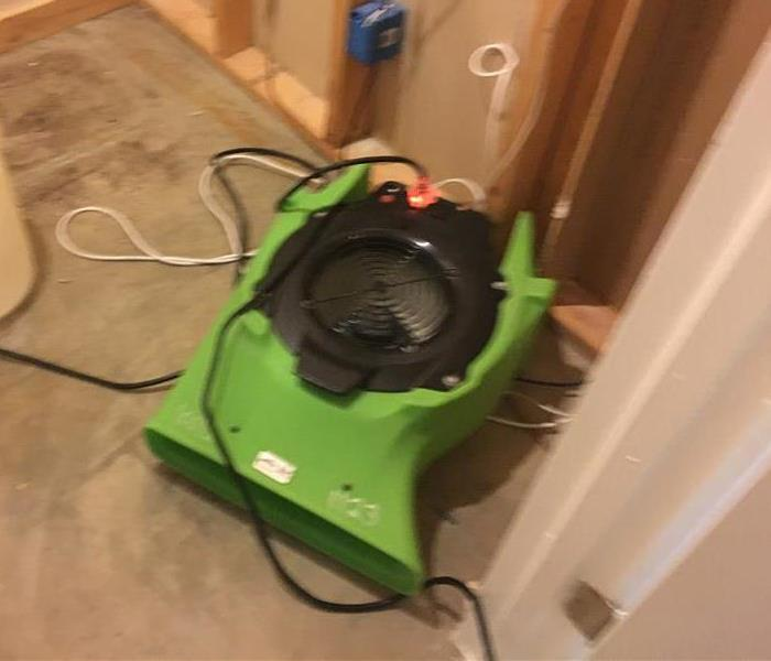 Green air movers in the process of drying a grey floor.