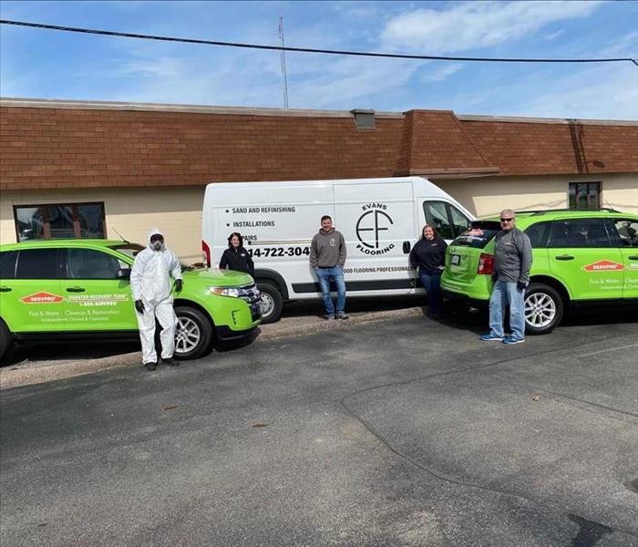 Employees posing with SERVPRO vehicles