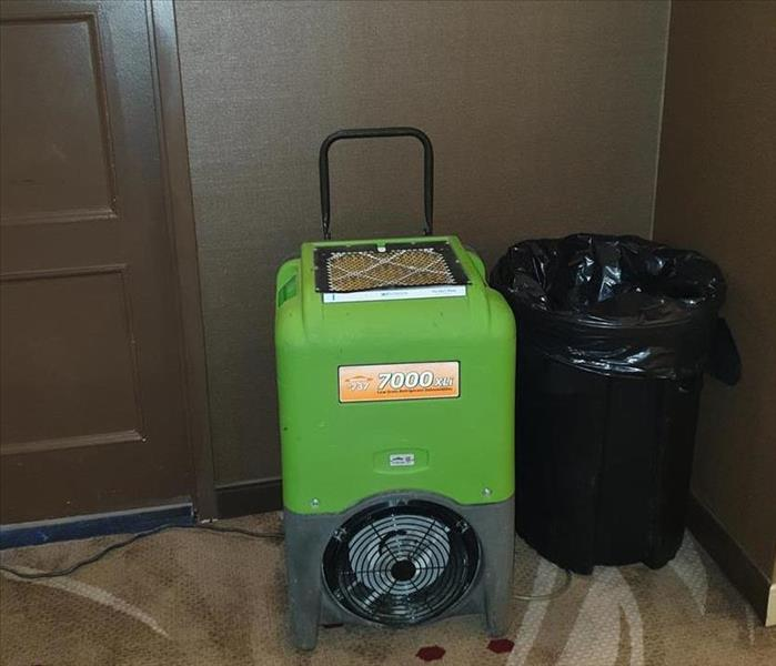 Green Dehumidifier up against a brown paneled wall.