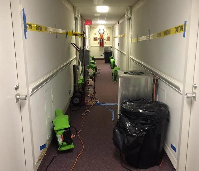 Hallway in a hotel with green air movers on the floor.