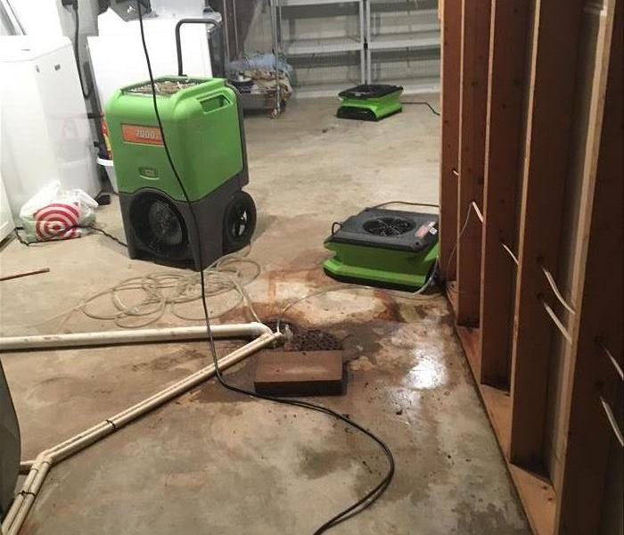 Air movers and air scrubbers on a concrete floor.