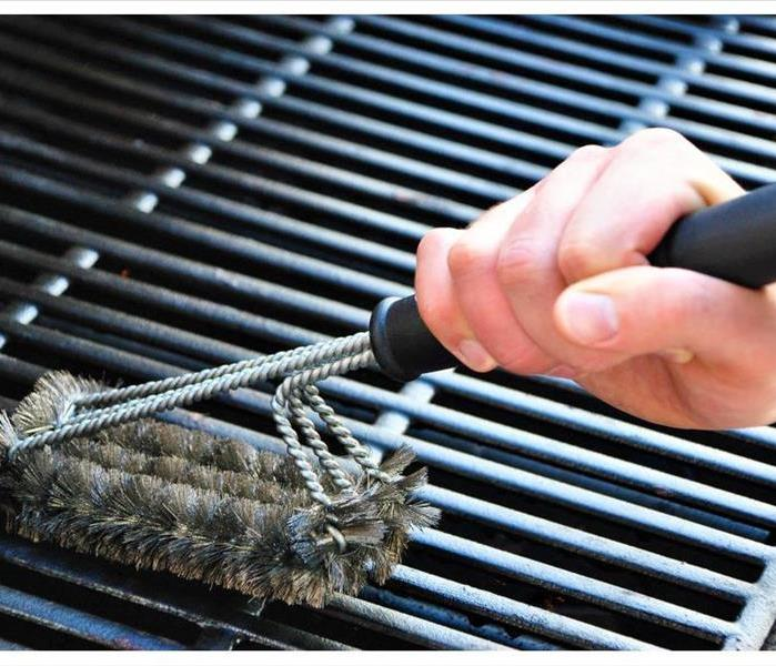The hands of someone cleaning a grill